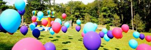 Multi Colored Balloons Floating on Grass